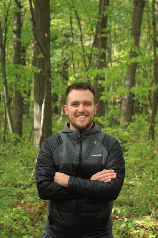 A picture of Eric Demers in front of a forest background